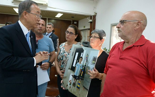 United Nations Secretary General Ban Ki-moon meets with residents from Kibbutz Nirim, including the grandparents of Daniel Tragerman -- Paulina, his grandmother, is holding a picture of Daniel -- on October 14, 2014. (Photo credit: Haim Zach/Flash90/GPO)