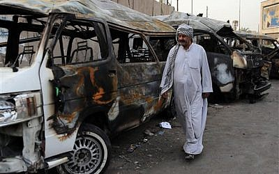 A man looks at the site of a car-bomb attack in the Shula neighborhood of Baghdad, Iraq, on October 12, 2014. (photo credit: AP/Karim Kadim)