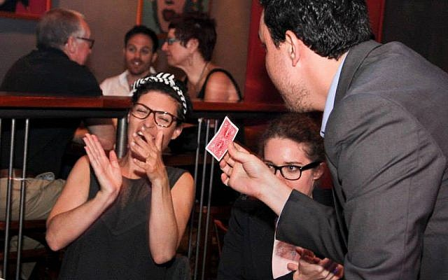 Magician Ran Gafner performs a close-up trick at a patron's table. (photo credit: photo by Shivi Isman)