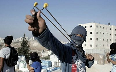 A Palestinian protester holds a slingshot during clashes with Israeli police (unseen) in a suburb of East Jerusalem on October 23, 2014. (photo credit: AFP PHOTO / Ahmad Gharabli)
