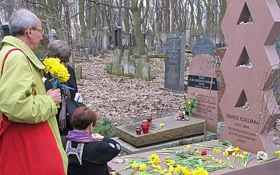 Observers placing daffodils at the grave of Marek Edelman, a commander of the Warsaw Ghetto uprising, in Warsaw's Jewish cemetery. (Ruth Ellen Gruber/JTA)