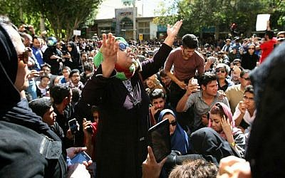 ILLUSTRATIVE PHOTO: Iranians take part in a protest in front of the judiciary building on October 22, 2014 in Isfahan,  in solidarity with women injured in a series of acid attacks (photo credit: AFP PHOTO/ISNA/Arya Jafari)