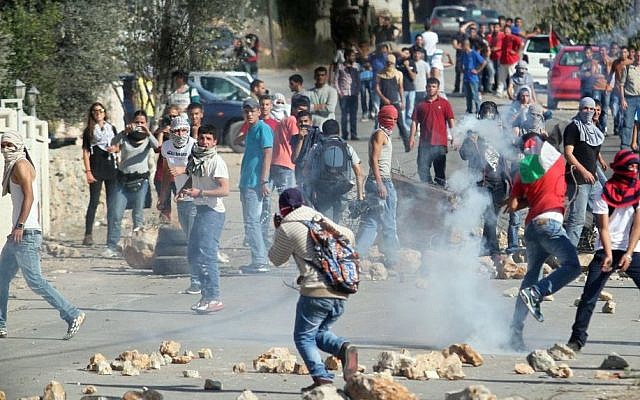 Illustrative photo of Palestinians clashing with Israeli soldiers, near the West Bank city of Ramallah, Sunday Oct. 26, 2014 (photo credit: STR/Flash90)