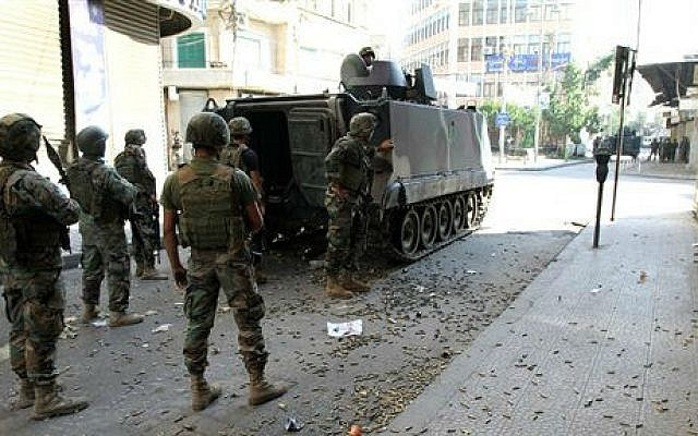 Lebanese army soldiers stand beside an armored vehicle with spent bullet casings littering the ground during clashes with Islamic militants, in the northern port city of Tripoli, Lebanon, Saturday, Oct. 25, 2014 (photo credit: AP)