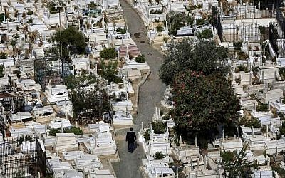 In this Oct. 14, 2014, photo, a Lebanese man, center, walks between graves at the overcrowded Bashoura cemetery for Muslim Sunnis in Beirut, Lebanon. The congested city of more than one million is cramped with cemeteries wedged into residential areas, increasingly forcing families to bury several members of the same family in one grave. Available land plots are extremely scarce and what is left is being used by developers to build luxury office towers and apartments. (Photo credit: AP/Hussein Malla)