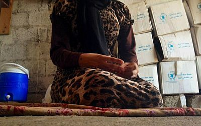 In this photo taken Wednesday, Oct. 8, 2014, a 15-year-old Yazidi girl captured by the Islamic State group and forcibly married to a militant in Syria sits on the floor of a one-room house she now shares with her family after escaping in early August, while speaking in an interview with The Associated Press in Maqluba, a hamlet near the Kurdish city of Dahuk, 260 miles (430 kilometers) northwest of Baghdad, Iraq. (AP Photo/Dalton Bennett)