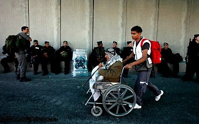 A young boy wheels an elderly Palestinian man past Israeli soldiers at a checkpoint on the outskirts of the West Bank city of Ramallah on August 05, 2011. (photo credit: Miriam Alster/Flash90)