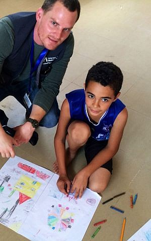 Adam Kawalek with a child, drawing a picture of his life during this summer's conflict and what he hopes his life will be like, at a community based organization in Gaza staffed by War Child. (Courtesy of Adam Kawalek)