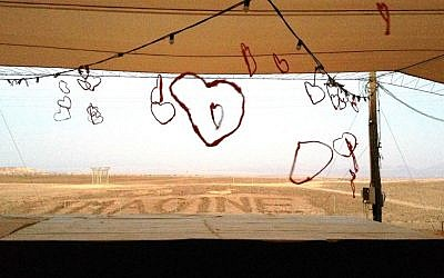 Peering through red hearts at the fields beyond the yoga/meditation space at Ashram in the Desert, one of the yoga sites for the weekend. (photo credit: Jessica Steinberg/Times of Israel)