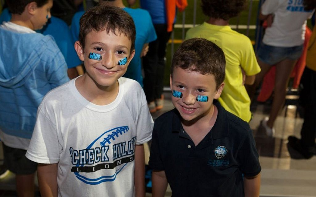 Students at Scheck Hillel Community Day School's homecoming football game, when its new synthetic turf field made its debut, Oct. 22, 2014. (Courtesy Scheck Hillel/JTA)