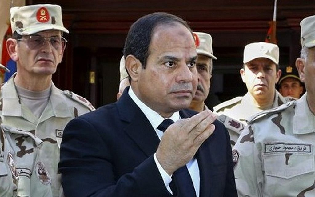 Egyptian President Abdel-Fattah el-Sissi speaks in front of the state-run TV ahead of a military funeral for troops killed in an assault in the Sinai Peninsula, as he stands with army commanders in Cairo, Egypt, October 25, 2014. (photo credit: AP/MENA, Mohammed Samaha)