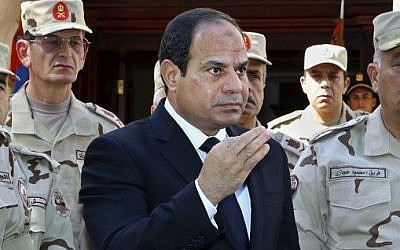 In this photo provided by Egypt's state news agency MENA, Egyptian President Abdel-Fattah el-Sissi speaks in front of the state-run TV ahead of a military funeral for troops killed in an assault in the Sinai Peninsula, as he stands with army commanders in Cairo, Egypt, Saturday, Oct. 25, 2014  (photo credit: AP Photo/MENA, Mohammed Samaha)