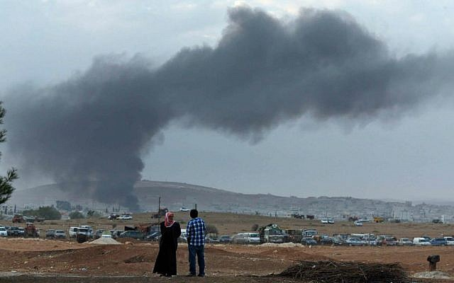 Residents of Mursitpinar on the outskirts of Suruc, at the Turkey-Syria border, watch as thick smoke rises following an airstrike by the US-led coalition in Kobani, Syria while fighting continued between Syrian Kurds and the Islamic State group, Tuesday, Oct. 14, 2014. (AP Photo/Lefteris Pitarakis)