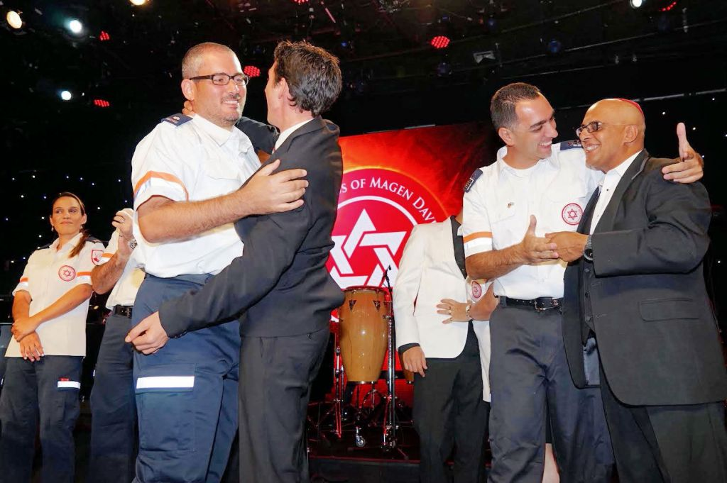At the Friends of Magen David Adom gala, MDA medic Oren Wachs (left) hugs the man he saved  -- Jehum Berman, and MDA medic Einav Auslan embraces Avinoam Levy, father of Yarin who was saved by Auslan and Neomi Zvi. (Orly Halevy)
