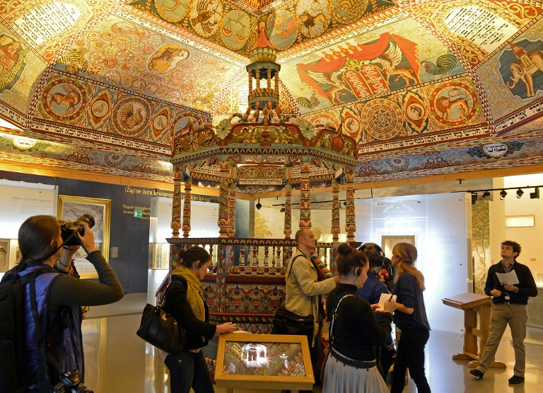 Visitors look at a reconstructed synagogue ceiling during an exhibition in the Museum of the History of Polish Jews, in Warsaw on October 21, 2014.(photo credit: AFP/Janek Skarzynski)