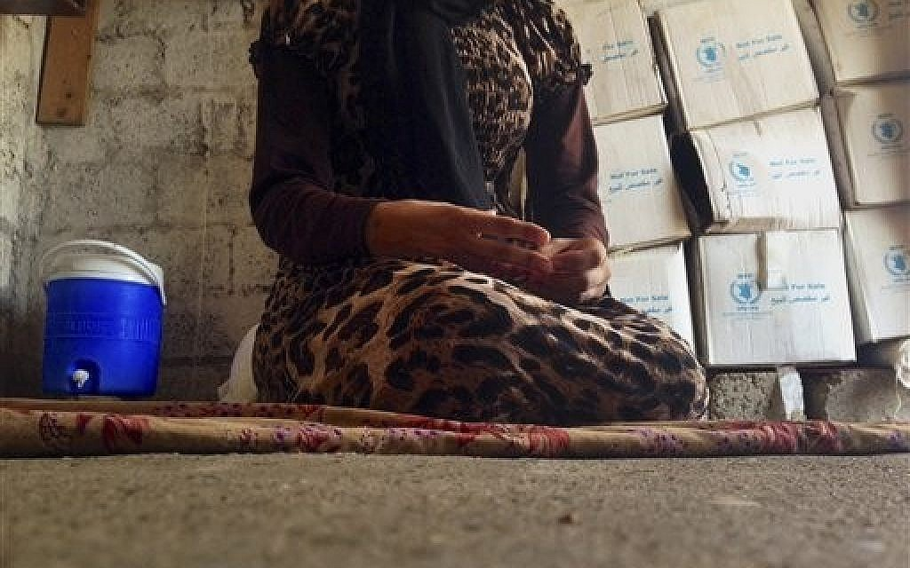In this photo taken Wednesday, Oct. 8, 2014, a 15-year-old Yazidi girl captured by the Islamic State group and forcibly married to a militant in Syria sits on the floor of a one-room house she now shares with her family after escaping in early August, while speaking in an interview with The Associated Press in Maqluba, a hamlet near the Kurdish city of Dahuk, 260 miles (430 kilometers) northwest of Baghdad, Iraq. Her face is not shown.  (photo credit: AP Photo/Dalton Bennett)