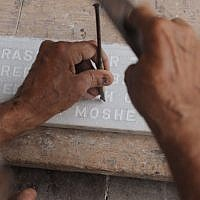In this photograph taken on August 21, 2014 Indian Muslim tombstone engraver Mohammad Abdul Yaseen, 74, chips inscriptions onto a stone slab at the Bene Israel Jewish cemetery in Mumbai. (photo credit: AFP PHOTO/ INDRANIL MUKHERJEE)