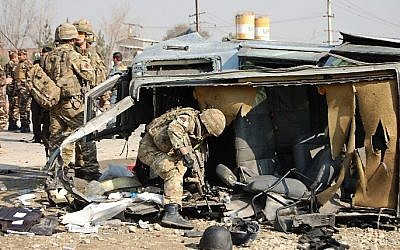 A NATO-led International Security Assistance Force (ISAF) soldier inspects a British embassy vehicle which was targeted in a suicide attack along the Kabul-Jalalabad road in Kabul on November 27, 2014. (photo credit: AFP/Daud Yardost)
