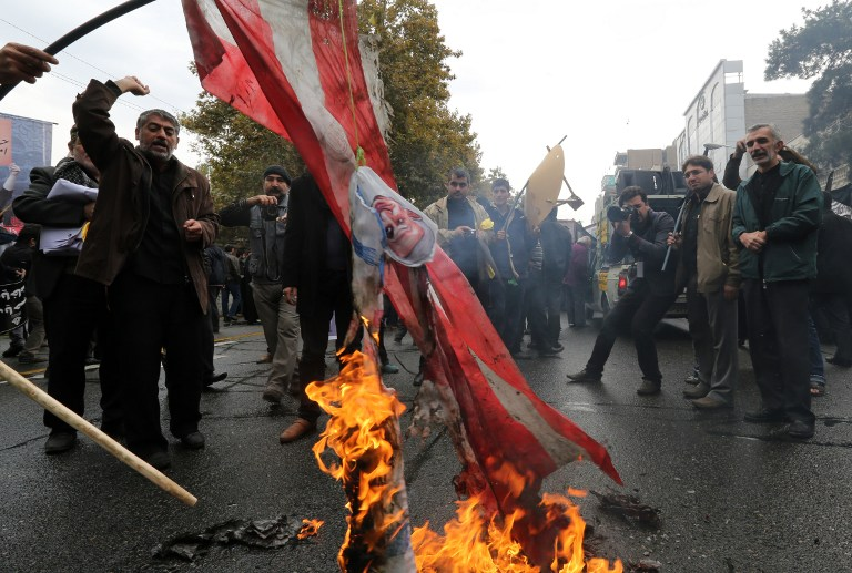 Iranians burn US flags outside the former US embassy in Tehran on November 4, 2014, during a demonstration to mark the anniversary of its storming by student protesters that triggered a hostage crisis. (photo credit: AFP/ATTA KENARE)