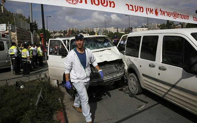 Israeli police and rescue workers inspect the car driven deliberately by a Palestinian man into a crowd of pedestrians in Jerusalem, on November 5, 2014. (photo credit: AFP/Gali Tibbon)