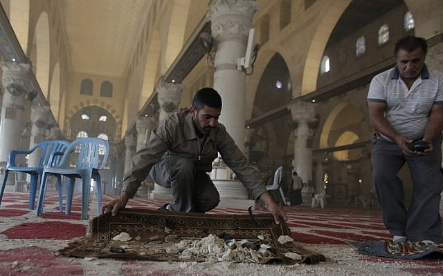 Palestinians clean up debris inside the Al-Aqsa Mosque, on November 5, 2014 following clashes between stone-throwing Palestinians and Israeli security forces. (photo credit:  AFP PHOTO/AHMAD GHARABLI)