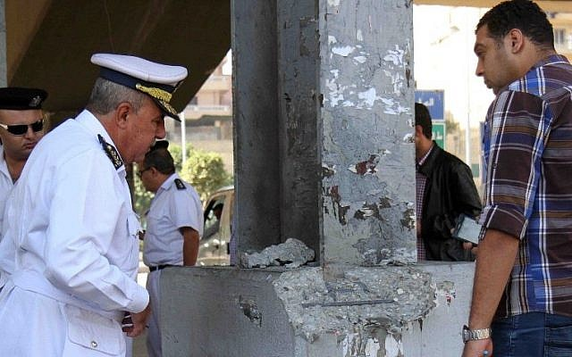Egyptian policemen inspect the site where a small bomb exploded near the al-Kobaa presidential palace in the northeast of Cairo on November 6, 2014.  (photo credit: AFP/STR)