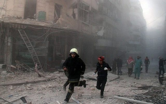 Emergency response teams rush to the scene of a reported barrel bomb attack by government forces in the al-Muasalat area in the northern Syrian city of Aleppo on November 6, 2014. (photo credit: AFP/AMC/Tamer al-Halabi)