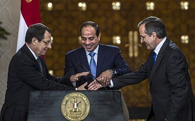 Egyptian President Abdel-Fattah al-Sissi (C), Cyprus' President Nicos Anastasiades (L) and Greek Prime Minister Antonis Samaras shake hands during a press conference following a meeting in Cairo on November 8, 2014. (Photo credit: AFP/Khaled Desouki)