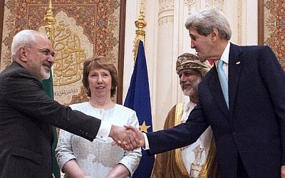 US Secretary of State John Kerry shakes hands with Iranian Foreign MinisterMohammad  Javad Zarif in Muscat, Oman on November 9, 2014 (photo credit: AFP Photo/Nicholas Kamm/Pool)