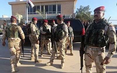 Iraqi army soldiers stand before a conference on fighting the Islamic State group attended by Iraq's tribal leaders, militiamen and members of the government, at the Al-Asad air base, in Iraq's mainly Sunni Anbar province, on November 11, 2014.  (photo credit: AFP/Ahmad al-Rubaye)