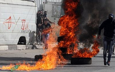 Palestinian protestors stand near burning tires during clashes with Israeli security forces in the West Bank city of Hebron on November 14, 2014 (Photo credit: Hazem Bader/AFP)