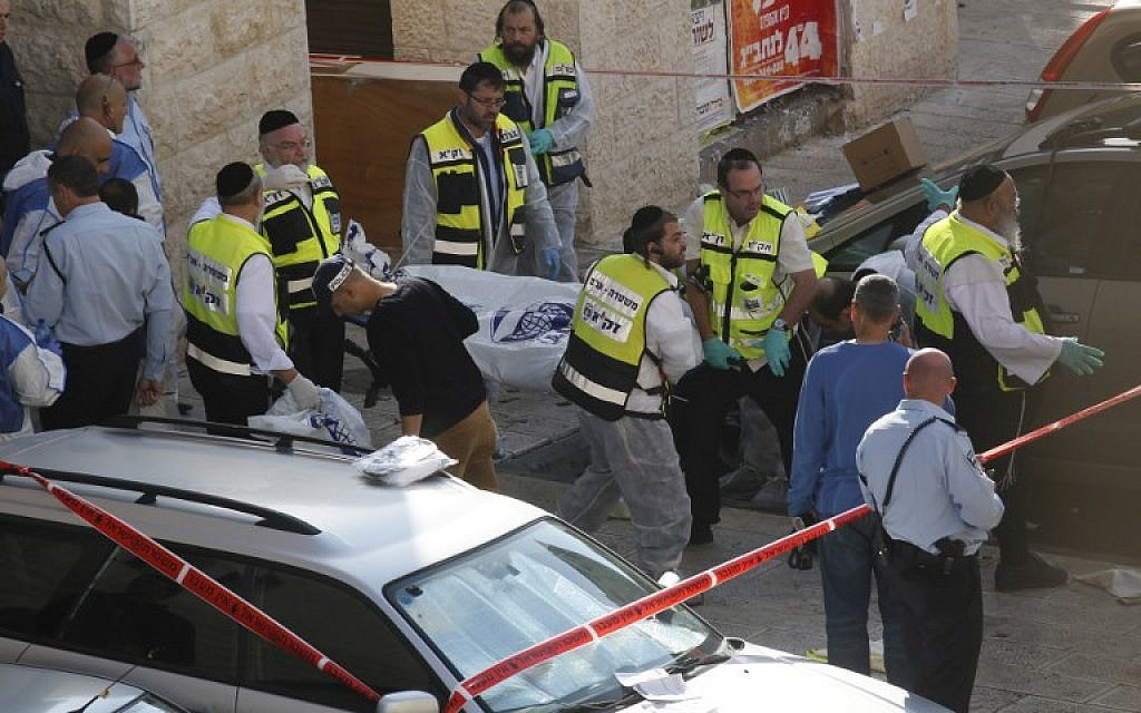 Israeli Zaka emergency services volunteers carry the body of a Palestinian assailant who was shot dead while attacking a synagogue in Jerusalem on November 18, 2014. (photo credit: AFP / GALI TIBBON)