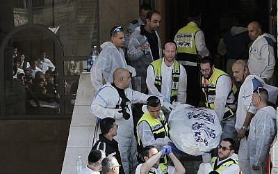 Israeli emergency services members carry a body at the scene of an attack at a synagogue in Jerusalem on November 18, 2014. (photo credit: AFP /AHMAD GHARABLI)