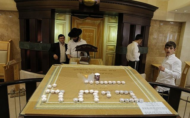 """Ultra-orthodox Jewish men stand inside the entrance of a synagogue that was attacked by two Palestinians earlier in the morning in the ultra-Orthodox Har Nof neighborhood in Jerusalem on November 18, 2014. The Hebrew writing in candles says """"House of God."""" (photo credit: AFP/JACK GUEZ)"""