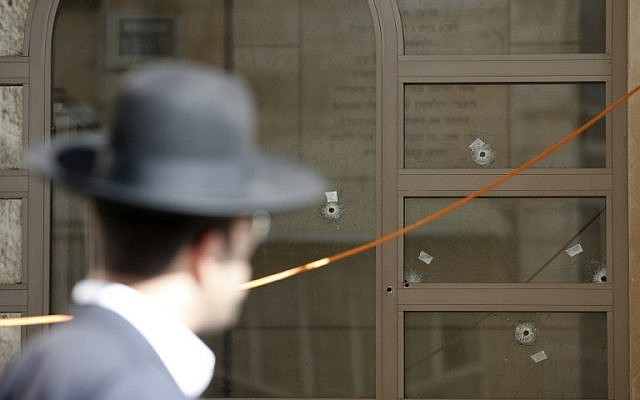A  Jewish man walks past a synagogue, with bullet holes in its window, that was attacked by two Palestinians earlier in the morning in the Har Nof neighborhood in Jerusalem on November 18, 2014. (photo credit: AFP/ JACK GUEZ)