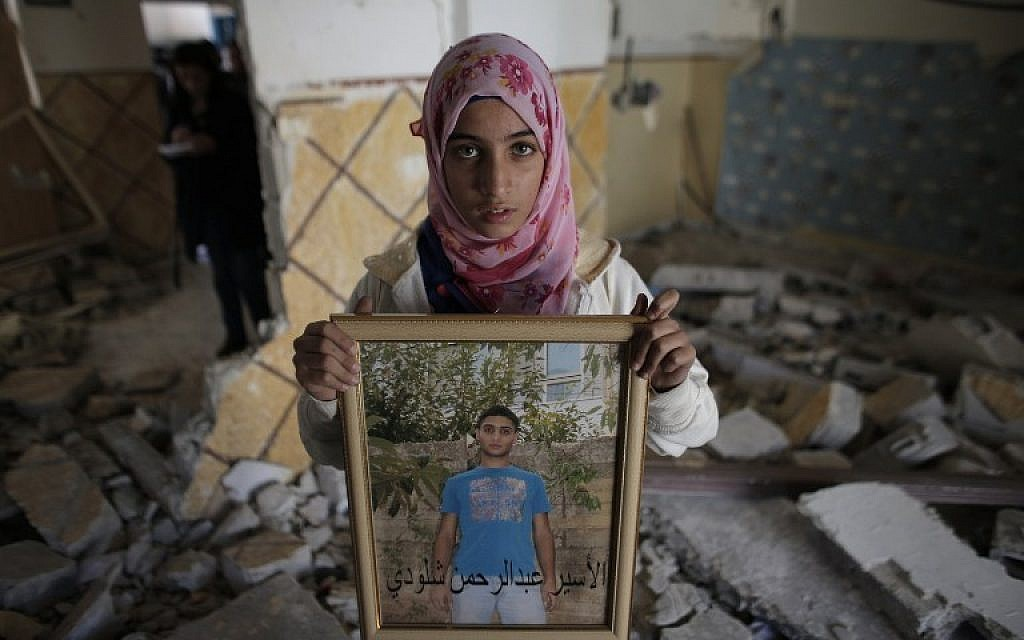 A relative of Abdel Rahman Shaludi, a Palestinian who killed two Israelis with his car last month, displays his portrait inside his family home after it was razed on November 19, 2014. (photo credit: AFP PHOTO/AHMAD GHARABLI)