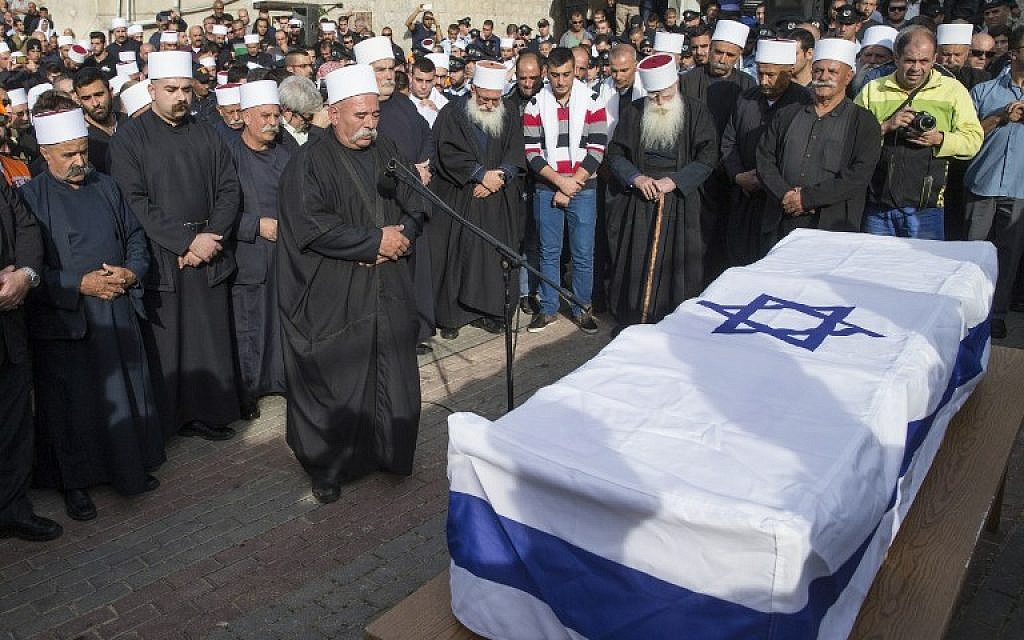 Friends,relatives, and religious dignitaries mourn near the coffin of Israeli police officer Zidan Saif, 30, a member of Israel's Druze minority, during his funeral in his northern home village of Yanuh-Jat, on November 19, 2014. Saif was killed the day before trying to intervene when two Palestinians armed with a gun and meat cleavers burst into a Jerusalem synagogue and killed four Israelis. (photo credit: AFP/JACK GUEZ)
