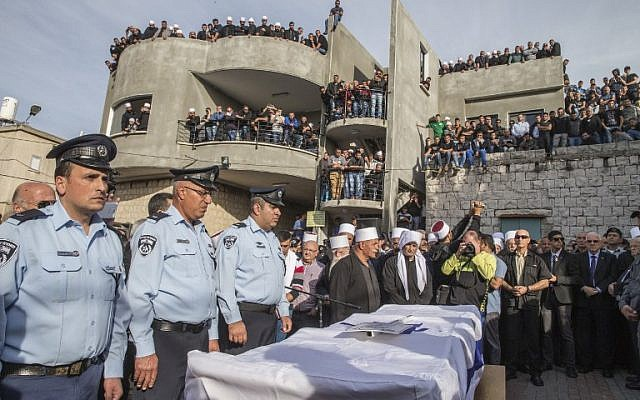 Police officers stand next to the coffin of Israeli police officer Zidan Saif, 30, a member of Israel's Druze minority, during his funeral in his northern home village of Yanuh-Jat, on November 19, 2014. Saif was killed during a terror attack on a Jerusalem synagogue the day before. (photo credit: AFP/Jack Guez)