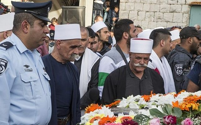 Friends, relatives and religious dignitaries mourn near the coffin of Israeli police officer Zidan Saif, 30, a member of Israel's Druze minority, during his funeral in his northern home village of Yanuh-Jat, on November 19, 2014. (photo credit: AFP/Jack Guez)
