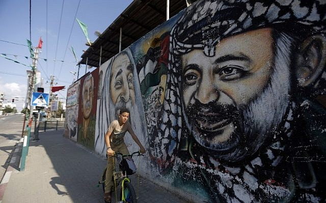 A Palestinian boy rides his bike past graffiti depicting (from L to R) founder of the Popular Front for the Liberation of Palestine (PFLP) George Habash, Hamas spiritual leader Sheikh Ahmed Yassin and Palestinian leader Yasser Arafat, on November 21, 2014 in Gaza City. (photo credit: AFP/MOHAMMED ABED)