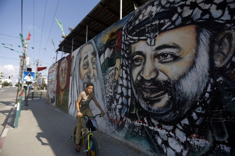 A Palestinian boy rides his bike past graffiti depicting (from L to R) late founder of the Popular Front for the Liberation of Palestine (PFLP) George Habash, late Hamas spiritual leader Sheikh Ahmed Yassin and late Palestinian leader Yasser Arafat, on November 21, 2014 in Gaza City. (photo credit: AFP/MOHAMMED ABED)