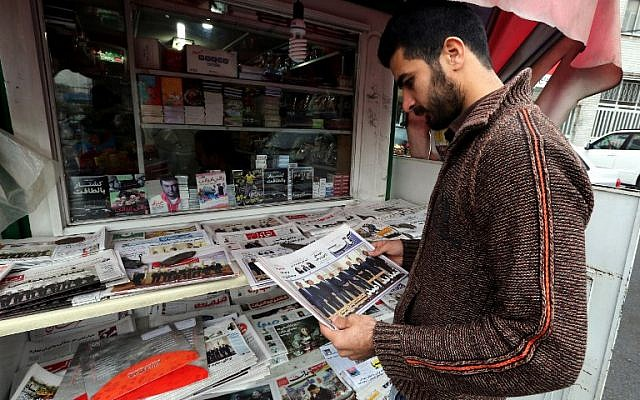 Illustrative: An Iranian man looks at newspapers displayed outside a kiosk in the capital Tehran on November 25, 2014. (AFP/ Atta Kenare)