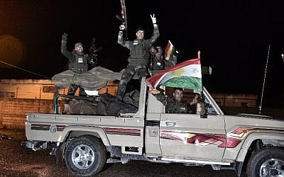 Kurdish peshmerga fighters gesture and wave a Kurdish flag from a military vehicle armed with a heavy infantry weapon as they ride towards the Syrian town of Kobani, also known as Ain al-Arab, from the border town of Suruc, in the Turkish southeastern Sanliurfa province, on October 31, 2014. (photo credit: AFP/STRINGER)