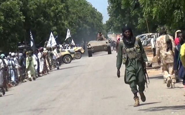 A screen capture taken on November 9, 2014 from a new Boko Haram video released by the Nigerian Islamist extremist group Boko Haram and obtained by AFP shows Boko Haram fighters parading with a tank in an unidentified town. (photo credit: AFP/HO/BOKO HARAM)