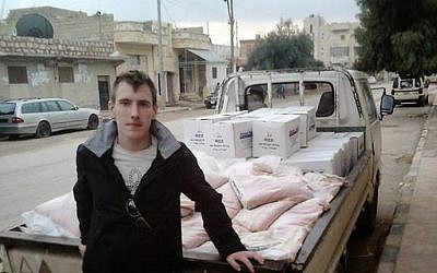 An undated photo of Peter Kassig leaning against a truck at unknown location. (photo credit: AFP/Kassig Family handout)