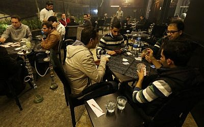 (FILES) - A file picture taken on November 15, 2014, Syrian men playing cards at a cafe in the Mogambo neighborhood on the government controlled side of Aleppo (photo credit: AFP/JOSEPH EID)