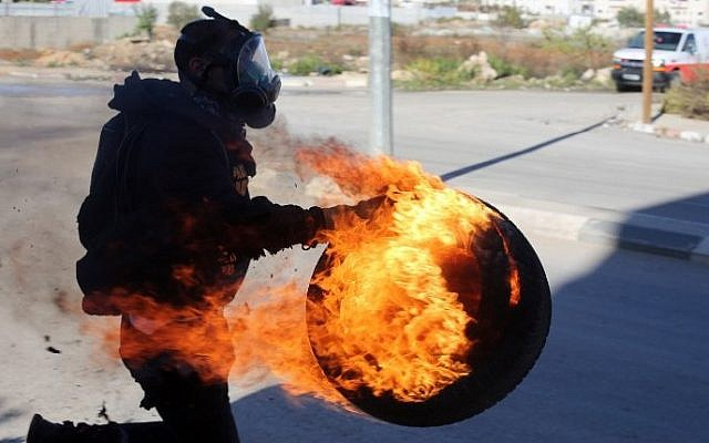 A Palestinian carries a lit tire during clashes between students from Birzeit University and Israeli soldiers (unseen) at the entrance to the Israeli Ofer military prison, near the West Bank village of Beitunia on November 6, 2014. (photo credit: AFP/Abbas Momani)