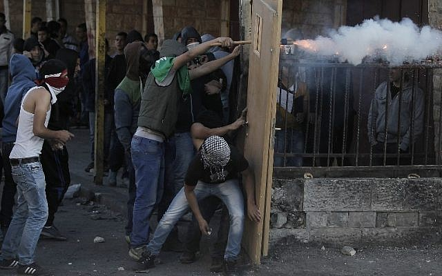 Masked Palestinian youths use doors as shield during clashes with Israeli security forces in the Palestinian refugee camp of Shuafat in east Jerusalem, on November 6, 2014. (photo credit: AFP PHOTO/ AHMAD GHARABLI)