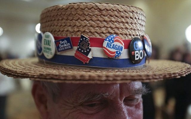 Hank Schwab of Atlanta (C), shows the campaign hat he's worn for the past 30 years at a gathering in support of Republican US Senate candidate David Perdue at the InterContinental Buckhead November 4, 2014 in Atlanta, Georgia. Perdue is running in a tight race against Democratic US Senate candidate Michelle Nunn (Photo credit: Jason Getz/Getty Images/AFP)