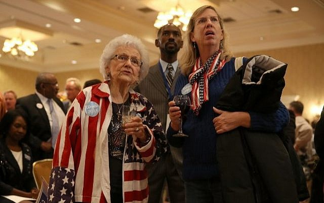 Marguerite Dawson (L) and Karen Sherrets attend the election night party for former Florida Governor and now Democratic gubernatorial candidate Charlie Crist as they watch a television screen showing early returns at the Vinoy hotel on November 4, 2014 in St. Petersburg, Florida. Crist is facing off against incumbent Republican Governor Rick Scott. (Photo credit: Joe Raedle/Getty Images/AFP)